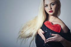 Piękna Blond kobieta z Czerwonym sercem. Piękno dziewczyna. Pokazuje miłość symbol. Walentynka dzień. Czarna suknia Fotografia Royalty Free