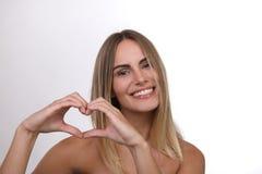 Piękna blond kobieta z nagimi ramionami tworzy serce z ona ręki obrazy royalty free
