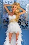 Piękna blond panna młoda w białej ślubnej sukni z bajecznie bardzo tęsk pociąg kryształy jest seksowna na schodkach opiera przeci Zdjęcie Royalty Free