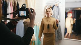 Piękna blond z włosami kobieta w wieczór sukni pozuje dla fotografa w ubraniowej butik sala wystawowej zbiory wideo