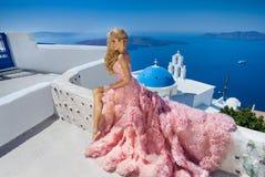 Piękna blond zbieg panna młoda w białej ślubnej sukni bajecznie z bardzo tęsk pociąg kryształy w ulicie na Santorini Zdjęcie Stock