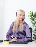Piękna blondynka, żeński obsługa klienta operator używa słuchawki Zdjęcia Royalty Free