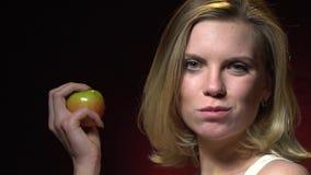 Piękna blondynka bierze kąsek zielony jabłko i zwroty kamera zdjęcie wideo