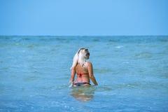 Piękna blondynka chodzi w wodę morską zdjęcia stock