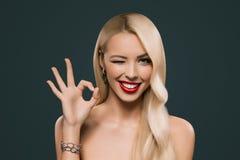 piękna blondynka mruga kobiety pokazuje ok znaka, obraz stock