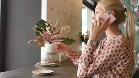 Pi?kna blondynka opowiada na telefonie kom?rkowym w kawiarni Smartphone kobieta ono u?miecha si?, m?wj?cy w kawiarni pi?kne m?od? zbiory wideo