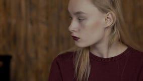 Piękna blondynka siedzi przy stołem w modnym miejscu zbiory wideo