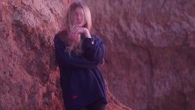Piękna blondynka stoi przeciw glinianej górze z bokeh skutkiem zbiory