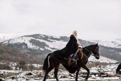 Piękna blondynka Viking w czarnym przylądku na horseback Fotografia Stock