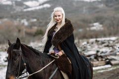 Piękna blondynka Viking w czarnym przylądku na horseback Obrazy Royalty Free