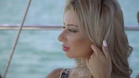 Piękna blondynka w makeup trzyma jej włosy i podziwia morze w pogodnej pogodzie zdjęcie wideo