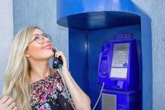 Piękna blondynka w szkłach trzyma telefonicznego odbiorcę w payphone Pięknie ono uśmiecha się, patrzejący niebo i opowiadający o, fotografia royalty free