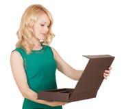Piękna blondynka w zieleni sukni otwiera pudełko Obrazy Royalty Free