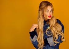 Piękna blondynka z długie włosy w drelichowy kurtki pozować Zdjęcia Stock