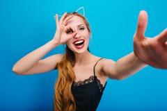 Piękna blondynka z kotów ucho ma zabawę przy przyjęciem, maskarada, karnawał, ono uśmiecha się, bierze selfie Falisty długie włos obrazy royalty free