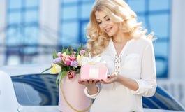 Piękna blondynka z kwiatami w prezenta pudełku obraz royalty free