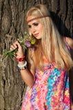 Piękna blondynka z kwiaty stać bezczynnie drzewem Obraz Royalty Free