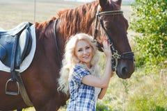 Piękna blondynki dziewczyna ściska jej brown konia w szkockiej kraty koszula Fotografia Stock
