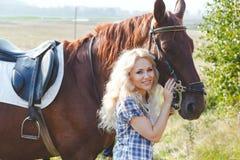 Piękna blondynki dziewczyna ściska jej brown konia w szkockiej kraty koszula Obrazy Stock