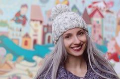 Piękna blondynki dziewczyna chodzi w mieście w pom pom kapeluszu z wino czerwieni wargami Zdjęcia Stock