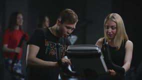 Piękna blondynki dziewczyna jest skrzętnym działaniem na ćwiczenie rowerze przychodzących wyjaśniać jej błąd w jej pracie na a ch zbiory wideo