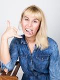 Piękna blondynki dziewczyna jest ubranym drelichowego koszulowego pokazuje jęzor i palce robi Shaka podpisywać Zdjęcie Royalty Free