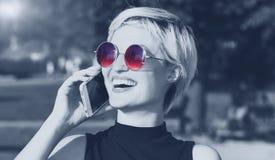 Piękna blondynki dziewczyna opowiada na telefonie i ono uśmiecha się zdjęcia stock