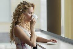 Piękna blondynki dziewczyna pije filiżankę gorąca kawa lub herbata w kawiarni Zdjęcia Stock