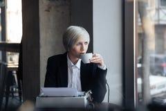 Piękna blondynki dziewczyna pije kawę w nowożytnej kawiarni Zdjęcie Stock