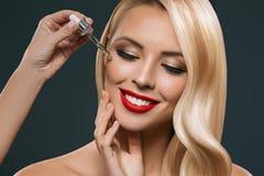 piękna blondynki dziewczyna stosuje traktowanie od pipety na twarzy, obraz stock