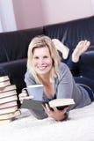 Piękna blondynki dziewczyna szczęśliwie czyta. Zdjęcia Royalty Free