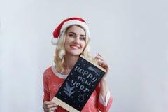 Piękna blondynki dziewczyna trzyma znaka z wpisowymi Szczęśliwymi ono uśmiecha się i nowym rokiem w Bożenarodzeniowym kapeluszu obraz stock