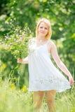 Piękna blondynki dziewczyna w biel sukni mienia bukiecie wildflow obraz royalty free