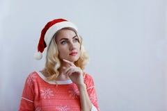 Piękna blondynki dziewczyna w boże narodzenie kapeluszu myśleć o bożych narodzeniach i ono uśmiecha się obraz stock
