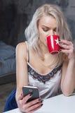 Piękna blondynki dziewczyna w domów ubraniach używa smartphone Zdjęcie Royalty Free