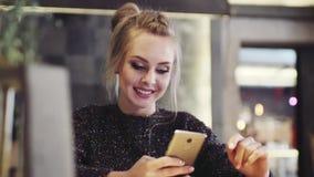 Piękna blondynki dziewczyna w eleganckim czarnym puloweru surfingu w internecie z jej telefonem komórkowym Zadziwiający makeup zbiory