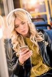 piękna blondynki dziewczyna w hełmofonach używać smartphone obrazy stock