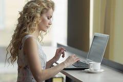 Piękna blondynki dziewczyna w smokingowym używa laptopie w kawiarni Zdjęcie Royalty Free
