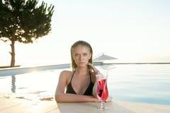 Piękna blondynki dziewczyna z świeżym sokiem w luksusowym basenie Fotografia Royalty Free