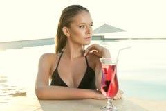 Piękna blondynki dziewczyna z świeżym sokiem w luksusowym basenie Obrazy Royalty Free