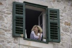 Piękna blondynki kobieta jest przyglądająca w odległość z filiżanką kawy Obraz Stock