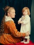 Piękna blondynki kobieta jest ubranym renaissance suknię bawić się z Li Fotografia Stock