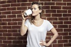 Piękna blondynki kobieta pije kawę w papierowym pustym filiżanki takeaw Obrazy Stock