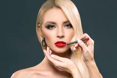 piękna blondynki kobieta robi czerwonym wargom z kosmetycznym ołówkiem, zdjęcie stock
