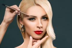 piękna blondynki kobieta stosuje brwi makeup, zdjęcia stock