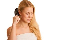 Piękna blondynki kobieta szczotkuje jej włosy jako szyldowego og włosiana opieka Obrazy Royalty Free
