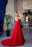 Piękna blondynki kobieta w czerwonej wieczór sukni w tła loft wnętrzu Mody sesja zdjęciowa. obraz stock