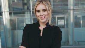 Piękna blondynki kobieta w eleganckim czarnym stroju, modnych akcesoriach i naturalnym makeup, stoi na zewnątrz lotniska zbiory wideo