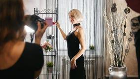 Piękna blondynki kobieta w koktajl sukni pozuje dla fotografa w ubraniowym butiku zdjęcie wideo