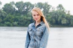 Piękna blondynki kobieta w niebieskich dżinsach z długie włosy na natury tle z kopii przestrzenią i fotografia royalty free